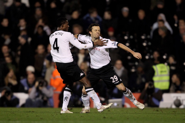Simon Davies of Fulham (R) celebrates with teammate John Pantsil after scoring the opening goal during the Barclays Premier League match between Fulham and West Bromwich Albion at Craven Cottage on January 4, 2011 in London, England.