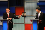 Presidential candidate Mike Huckabee (L)  speaks while Louisiana Governor Bobby Jindal listens during the Republican Presidential Debate sponsored by Fox Business and the Wall Street Journal at the Milwaukee Theatre November 10, 2015 in Milwaukee, Wisconsin. The fourth Republican debate is held in two parts, one main debate for the top eight candidates, and another for four other candidates lower in the current polls.