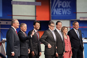 Republican presidential candidates (L-R) Jim Gilmore, Sen. Lindsey Graham (R-SC), Louisiana Gov. Bobby Jindal, Rick Perry, Rick Santorum, Carly Fiorina and George Pataki pose for photographs at the beginning of a presidential forum hosted by FOX News and Facebook at the Quicken Loans Arena August 6, 2015 in Cleveland, Ohio. The seven GOP candidates were selected to participate in the forum based on their rank in an average of the five most recent national political polls.