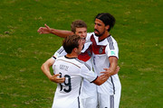 Thomas Mueller of Germany (C) reacts after scoring his team's first goal on a penalty kick with Mario Goetze (L) and Sami Khedira (R) during the 2014 FIFA World Cup Brazil Group G match between Germany and Portugal at Arena Fonte Nova on June 16, 2014 in Salvador, Brazil.