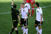 Miroslav Klose of Germany (top) is awarded a second yellow card and is sent off by referee Alberto Undiano as Bastian Schweinsteiger of Germany appeals during the 2010 FIFA World Cup South Africa Group D match between Germany and Serbia at Nelson Mandela Bay Stadium on June 18, 2010 in Port Elizabeth, South Africa.