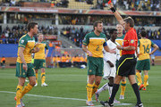 Harry Kewell (L) and Lucas Neill of Australia argue with the referee Roberto Rosetti as he sends off Kewell for handball and awards Ghana a penalty during the 2010 FIFA World Cup South Africa Group D match between Ghana and Australia at the Royal Bafokeng Stadium on June 19, 2010 in Rustenburg, South Africa.