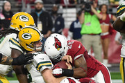 Quarterback Aaron Rodgers #12 of the Green Bay Packer is sacked by outside linebacker Alex Okafor #57 and cornerback Jerraud Powers #25 of the Arizona Cardinals at University of Phoenix Stadium on December 27, 2015 in Glendale, Arizona. The Cardinals won 38-8.