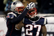 Cornerback Kyle Arrington #27 of the New England Patriots (R) is congratulated for scoring a touchdown after intercepting the ball and running 36 yards by teammate safety Brandon Meriweather #31 during the third quarter of the game against the Green Bay Packers at Gillette Stadium on December 19, 2010 in Foxboro, Massachusetts.