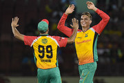 In this handout image provided by CPL T20, Chris Green (R) and Imran Tahir (L) of Guyana Amazon Warriors celebrates the dismissal of Evin Lewis of St Kitts & Nevis Patriots during the Hero Caribbean Premier League match 2 between Guyana Amazon Warriors and St Kitts & Nevis Patriots at Guyana National Stadium on August 9, 2018 in Providence, Guyana.