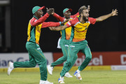 In this handout image provided by CPL T20, Imran Tahir (R), Jason Mohammed (L) and Keemo Paul (C) of Guyana Amazon Warriors celebrate the dismissal of Glenn Phillips of Jamaica Tallawahs during match 29 of the Hero Caribbean Premier League match between Guyana Amazon Warriors and Jamaica Tallawahs at Guyana National Stadium on September 8, 2018 in Providence, Guyana.