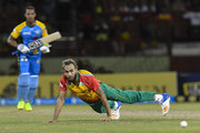 In this handout image provided by CPL T20, Imran Tahir (R) of Guyana Amazon Warriors attempts to stop Lendl Simmons (L) of St Lucia Stars during match 4 of the Hero Caribbean Premier League between Guyana Amazon Warriors and St Lucia Stars at Guyana National Stadium on August 11, 2018 in Providence, Guyana.