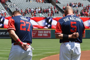 Mike Trout #27 and Albert Pujols #5 of the Los Angeles Angels stand for the National Anthem before the start of the game against the Houston Astros at Angel Stadium on August 26, 2018 in Anaheim, California. All players across MLB will wear nicknames on their backs as well as colorful, non-traditional uniforms featuring alternate designs inspired by youth-league uniforms during Players Weekend.