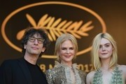 (From L) British novelist Neil Gaiman, Australian actress Nicole Kidman and US actress Elle Fanning pose as they arrive on May 21, 2017 for the screening of the film 'How to talk to Girls at Parties' at the 70th edition of the Cannes Film Festival in Cannes, southern France.  / AFP PHOTO / Alberto PIZZOLI