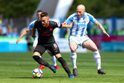 Aaron Ramsey of Arsenal battles for possession with Aaron Mooy of Huddersfield Town during the Premier League match between Huddersfield Town and Arsenal at John Smith's Stadium on May 13, 2018 in Huddersfield, England.