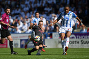 Aaron Ramsey of Arsenal in action as Mathias Jorgensen of Huddersfield Town looks on during the Premier League match between Huddersfield Town and Arsenal at John Smith's Stadium on May 13, 2018 in Huddersfield, England.