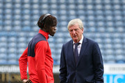 Wilfried Zaha of Crystal Palace (L) and Roy Hodgson, Manager of Crystal Palace speak ahead of the Premier League match between Huddersfield Town and Crystal Palace at John Smith's Stadium on September 15, 2018 in Huddersfield, United Kingdom.