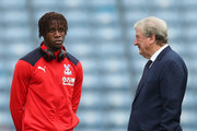 Wilfried Zaha of Crystal Palace (R) and Roy Hodgson, Manager of Crystal Palace speak ahead of the Premier League match between Huddersfield Town and Crystal Palace at John Smith's Stadium on September 15, 2018 in Huddersfield, United Kingdom.