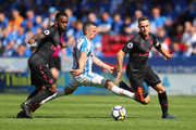 Jonathan Hogg of Huddersfield Town tries to beat Alexandre Lacazette and Aaron Ramsey of Arsenal during the Premier League match between Huddersfield Town and Arsenal at John Smith's Stadium on May 13, 2018 in Huddersfield, England.