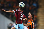 Aaron Cresswell of West Ham United outjumps Hatem Ben Arfa of Hull City during Barclays Premier League match between Hull City and West Ham United at KC Stadium on September 15, 2014 in Hull, England.