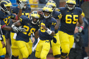 Fitzgerald Toussaint #28 of the Michigan Wolverines celebrates a third quarter touchdown with Denard Robinson #16 and the rest of his offensive teammates while playing the Illinois Fighting Illini at Michigan Stadium on October 13, 2012 in Ann Arbor, Michigan.  Michigan won the game 45-0.
