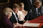 Prince Willem-Alexander of the Netherlands signs the Act of Abdication during the abdication ceremony for his mother Queen Beatrix of the Netherlands (L) as his wife Princess Maxima of the Netherlands looks on in the Moseszaal at the Royal Palace on April 30, 2013 in Amsterdam. Queen Beatrix of the Netherlands is abdicating the throne after a 33 year reign and hands the throne to her son Prince Willem-Alexander who will be sworn in later at the Nieuwe Kerk ahead of a joint session of parliament.