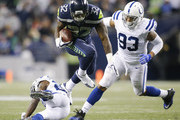 Running back Chris Carson #32 of the Seattle Seahawks jump over Nate Hairston #27 of the Indianapolis Colts while being pursued by Jabaal Sheard #93 in the third quarter of the game at CenturyLink Field on October 1, 2017 in Seattle, Washington.