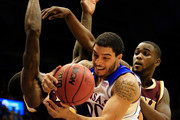 Niko Roberts #20 of the Kansas Jayhawks battles A.J. English #5 and Deshawn Gomez #0 of the Iona Gaels for a loose ball during the game at Allen Fieldhouse on November 19, 2013 in Lawrence, Kansas.