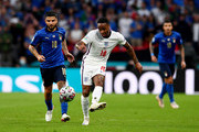 Raheem Sterling of England makes a pass whilst under pressure from Lorenzo Insigne of Italy during the UEFA Euro 2020 Championship Final between Italy and England at Wembley Stadium on July 11, 2021 in London, England.