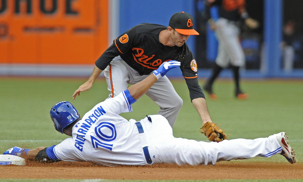 Edwin Encarnacion #10 of the Toronto Blue Jays slides safely into second base as J.J. Hardy #2 of the Baltimore Orioles covers the bag during MLB game action June 21, 2013 at Rogers Centre in Toronto, Ontario, Canada.