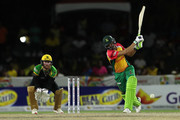 FORT LAUDERDALE, UNITED STATES- AUGUST 18: In this handout image provided by CPL T20, Shoaib Malik of Guyana Amazon Warriors plays an attacking shot as Glenn Phillips of Jamaica Tallawahs looks on during the Hero Caribbean Premier League match between Jamaica Tallawahs and Guyana Amazon Warriors at Central Broward Regional Park on August 18, 2018 in Florida, United States.