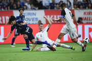 Takumi Minamino of Japan is tackled by Juan Pablo of Costa Rica during the international friendly match between Japan and Costa Rica at Suita City Football Stadium on September 11, 2018 in Suita, Osaka, Japan.