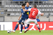 Hotaru Yamaguchi of Japan and Richard Ortiz of Paraguay compete for the ball during the international friendly match between Japan and Paraguay at Tivoli Stadion on June 12, 2018 in Innsbruck, Austria.