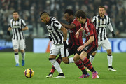 Arturo Vidal (L) of Juventus FC is challenged by Michael Essien (C) and Andrea Poli of AC Milan during the Serie A match between Juventus FC and AC Milan at Juventus Arena on February 7, 2015 in Turin, Italy.