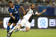 Gonzalo Higuain of Juventus is tackled by Danilo D'Ambrosio of FC Internazionale during the International Champions Cup match between Juventus and FC Internazionale at the Nanjing Olympic Center Stadium on July 24, 2019 in Nanjing, China.