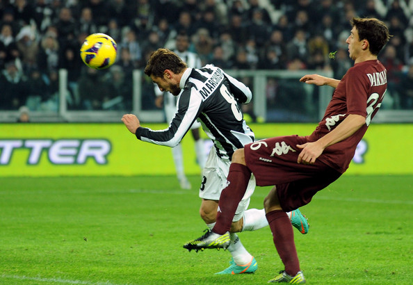 Claudio Marchisio (L) of Juventus scores the opening goal during the Serie A match between Juventus and Torino FC at Juventus Arena on December 1, 2012 in Turin, Italy.