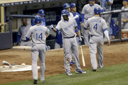 Omar Infante #14 and Alex Gordon #4 of the Kansas City Royals celebrate with Alcides Escobar #2 after scoring on a two-run single off the bat of Chris Young in the fourth inning of an interleague game against the Milwaukee Brewers at Miller Park on June 16, 2015 in Milwaukee, Wisconsin.