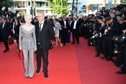 """French director Tonie Marshall (L) and French fashion designer Jean-Paul Gaultier pose as they arrive on May 15, 2016 for the screening of the film """"Mal de Pierres (From the Land of the Moon)"""" at the 69th Cannes Film Festival in Cannes, southern France.  / AFP / ALBERTO PIZZOLI"""