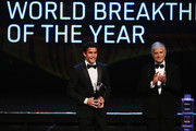 Motor cyclist Marc Marquez speaks with his Laureus World Breakthrough of the Year award from Laureus Academy members Giacomo Agostini  during the 2014 Laureus World Sports Award show at the Istana Budaya Theatre on March 26, 2014 in Kuala Lumpur, Malaysia.