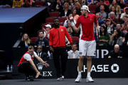 Team World John Isner of the United States celebrates a point with teammates Team World Jack Sock of the United States and Team World Frances Tiafoe of the United States during their Men's Singles match against Team Europe Roger Federer of Switzerland on day three of the 2018 Laver Cup at the United Center on September 23, 2018 in Chicago, Illinois.