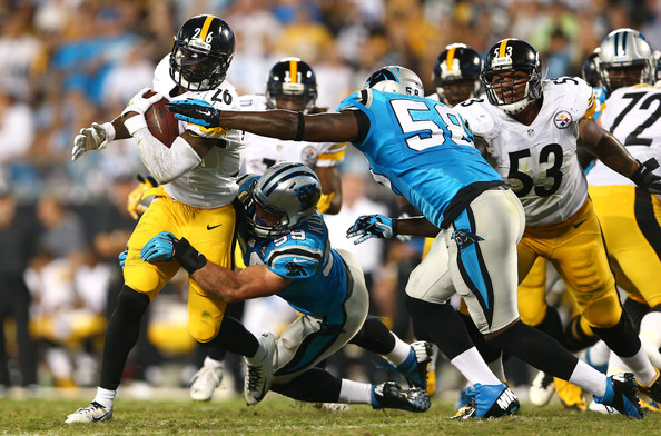 Le'Veon Bell Teammates Thomas Davis #58 and Luke Kuechly #59 of the Carolina Panthers tackle Le'Veon Bell #26 of the Pittsburgh Steelers during the game at Bank of America Stadium on September 21, 2014 in Charlotte, North Carolina.