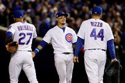 Addison Russell #27, Javier Baez #9, and Anthony Rizzo #44 of the Chicago Cubs meet during a pitching change in the seventh inning against the Los Angeles Dodgers during game four of the National League Championship Series at Wrigley Field on October 18, 2017 in Chicago, Illinois.