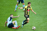 Michael McGlinchey of the Phoenix is tackled by Luke Wilkshire of Sydney FC during the round 12 A-League match between the Wellington Phoenix and Sydney FC at Westpac Stadium on December 23, 2017 in Wellington, New Zealand.
