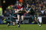 Rory Scannell of Munster tackled by Dan Cole (l) and Manu Tuilagi of Leicester Tigersduring the European Rugby Champions Cup match between Leicester Tigers and Munster Rugby at Welford Road on December 17, 2017 in Leicester, England.