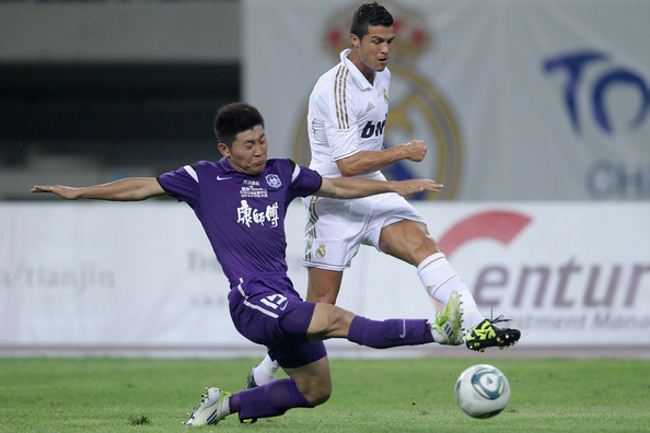 Tianjin Teda v Real Madrid - Real Madrid's China Tour [player,sports,sports equipment,football player,soccer player,team sport,ball game,soccer,football,sport venue,cristiano ronaldo,liao bochao,right,ball,left,water drop stadium,real madrid,tianjin teda,china tour,match]