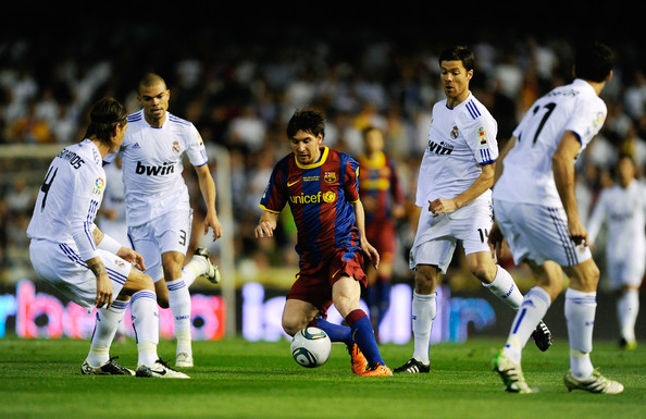 Lionel Messi Lionel Messi of FC Barcelona (C) holds off a challenge by  Xabi Alonso of Real Madrid (2ndR) during the Copa del Rey Final between Real Madrid and Barcelona at Estadio Mestalla on April 20, 2011 in Valencia, Spain.