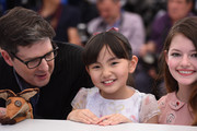 """(L-R) Director Mark Osborne,  Rio Suzuki  and Mackenzie Foy attend the """"Little Prince"""" (""""Le Petit Prince"""") Photocall-  during the 68th annual Cannes Film Festival on May 22, 2015 in Cannes, France."""