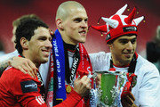Maxi Rodriguez, Martin Skrtel and Luis Suarez of Liverpool celebrate with the trophy after victory in the Carling Cup Final match between Liverpool and Cardiff City at Wembley Stadium on February 26, 2012 in London, England. Liverpool won 3-2 on penalties.
