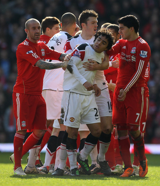 Rafael of Manchester United is restrained following his challenge on Lucas of Liverpool during the Barclays Premier League match between Liverpool and Manchester United at Anfield on March 6, 2011 in Liverpool, England.