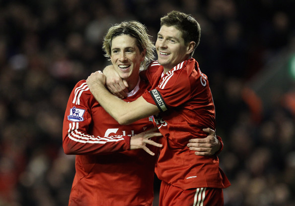 Fernando Torres of Liverpool is congratulated by team mate Steven Gerrard (R) after scoring his team's second goal during the Barclays Premier League match between Liverpool and Wigan Athletic at Anfield on December 16, 2009 in Liverpool, England.