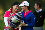 Lorena Ochoa of Mexico (blue sweater) presents Christina Kim of the United States with the champions trophy after Kim's victory at the 2014 Lorena Ochoa Invitational presented by Banamex at Club de Golf Mexico on November 16, 2014 in Mexico City, Mexico.