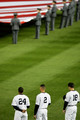 Robinson Cano #24, Derek Jeter #2 and Johnny Damon #18 of the New York Yankees stand for the national anthem before Game One of the ALCS against of the Los Angeles Angels of Anaheim during the 2009 MLB Playoffs at Yankee Stadium on October 16, 2009 in New York, New York.