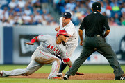 Martin Maldonado #12 of the Los Angeles Angels of Anaheim is tagged out by Matt Holliday #17 of the New York Yankees at second base during a second inning steal attempt at Yankee Stadium on June 21, 2017 in the Bronx borough of New York City.