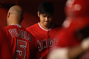 Shohei Ohtani #17 of the Los Angeles Angels crosses Albert Pujols #5 in the dugout during the eighth inning of the MLB game against the Arizona Diamondbacks at Chase Field on August 21, 2018 in Phoenix, Arizona.