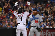 Ketel Marte #4 of the Arizona Diamondbacks celebrates after hitting an RBI triple during the first inning as Justin Turner #10 of the Los Angeles Dodgers looks on at Chase Field on September 24, 2018 in Phoenix, Arizona.